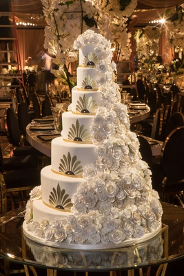 Art deco design wedding cake gold white cascading sugar flowers rose frosting on glass table wedding