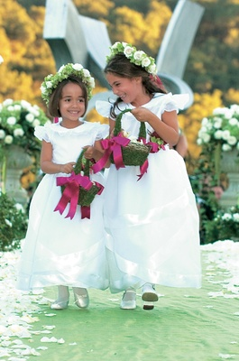 Flower girls in white dresses with flower crowns