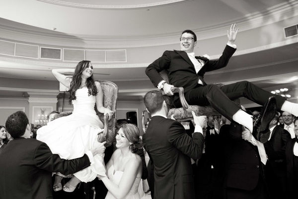 Black and white photo of bride and groom during hora wedding dance Jewish tradition