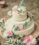 three layer wedding cake ivory frosting decorated with greenery pink white flowers on wood stand