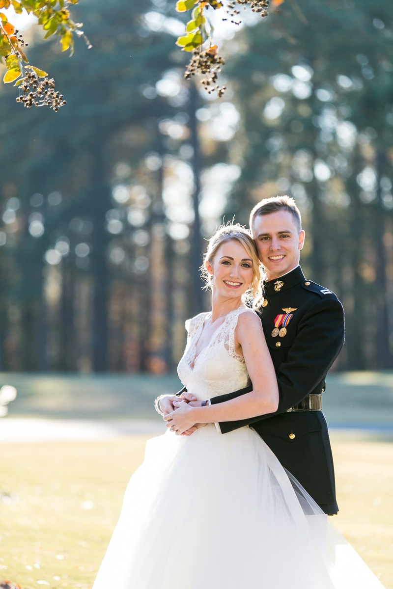 Bride in Monique Lhuillier dress and groom in dress blues