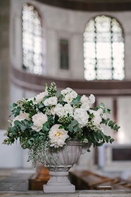 stone urn filled with white flowers and green branches