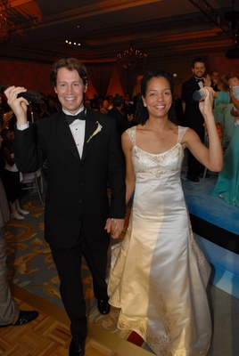 Bride in a Reem Acra gown with groom in a black tuxedo at wedding reception
