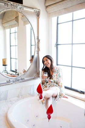 Bride in flower print robe getting ready in bridal suite by bathtub in louboutins red sole