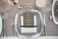 White table, grey linen, silver metallic charger plate, white goblet contemporary reception