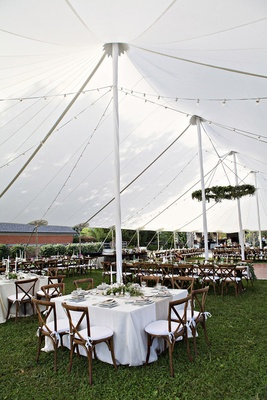 Farm wedding reception on grassy area with white open-sided tent, rustic chairs, white tablecloths