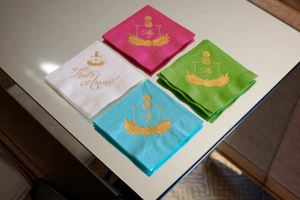 four different colors of cocktail napkins, white, turquoise, green, pink napkins with gold embossed