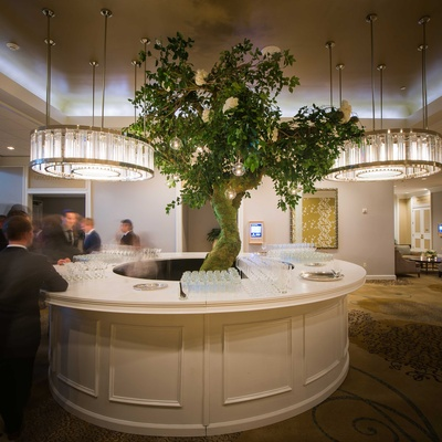 a round bar under round chandeliers with a large tree rising from the center