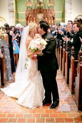 bride in inbal dror mermaid wedding dress, cathedral veil, groom in all black tuxedo, kiss in aisle