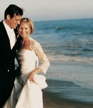 Groom and bride smile on sand in front of ocean