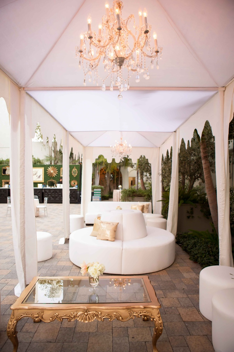 White ottoman, settees, and benches in cabana with chandelier and gold coffee table