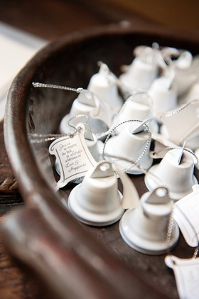 Miniature white bell wedding favors with note from bride and groom