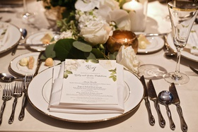 wedding reception place setting flower print menu on napkin white flower gold candle votives
