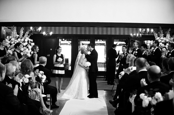 Black and white photo of bride in a strapless Vera Wang dress, veil kisses groom in a black tuxedo