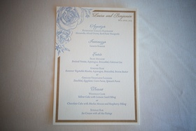 ivory invitation with gold trim and blue floral design