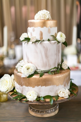 wedding cake with gold paint and brushstroke details with white flowers