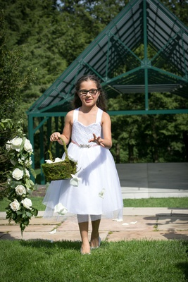 Flower girl in white tank dress tossing flower petals moss basket green lawn glasses