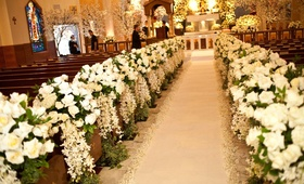 Church pews decorated with ivory floral arrangements