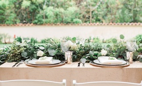 Garden wedding reception table with greenery runner, white roses, golden tablecloth, silver tumblers
