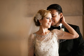 Bride in a beaded Jenny Packham dress, sparkling headpiece, and veil with groom in black tuxedo