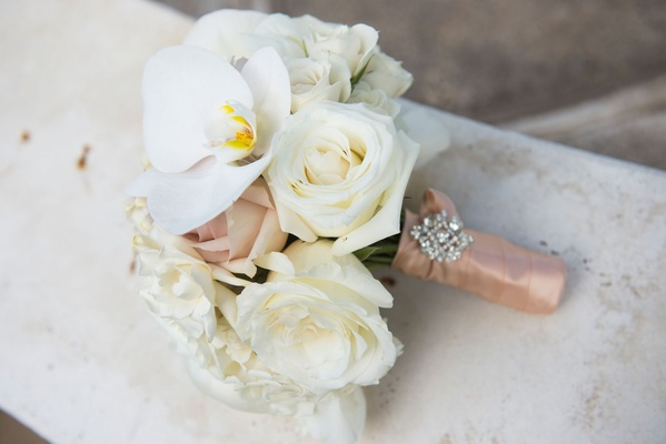 Bridesmaid bouquet with orchids and roses, wrapped with a blush ribbon and embellished with a jewel