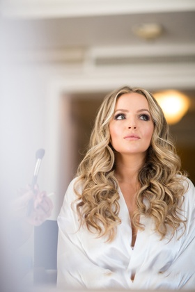 bride with softly curled blonde hair and makeup with dramatic eyes getting makeup done