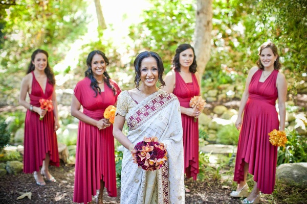 Bridesmaids in asymmetrical red dresses with bride in a white sari