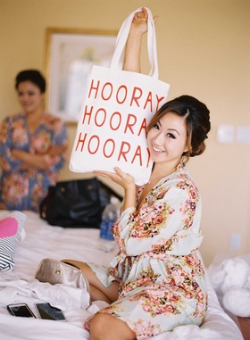 Bride in bridal suite with Hooray tote bag wearing flower print getting ready robe