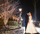 Bride in Oscar de la Renta wedding dress kissing groom at night around Christmas decorations