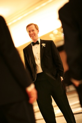 Groom in a black tuxedo with a matching bow tie and a white boutonniere