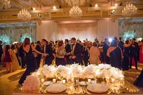 Wedding reception guests on dance floor view from bride and groom seats in ballroom chandeliers