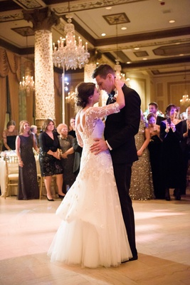 First dance bride in monique lhuillier wedding dress bustle updo chandeliers guests watching