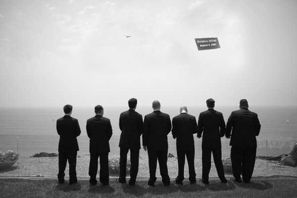 Black and white photo of groomsmen and ocean