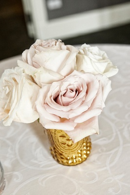 ivory and blush roses in a gold vase at wedding cocktail table