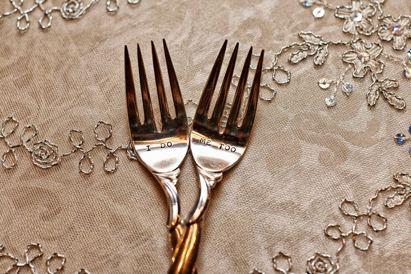 "Bride and groom's cake forks inscribed with ""I do"" and ""Me too"" on tablecloth with silver embroidery"