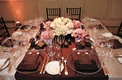 Chocolate-colored tablecloths and pink rose centerpieces