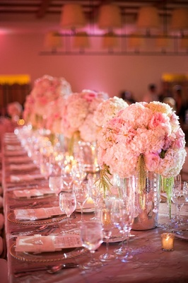 Long rectangular table topped with pink florals