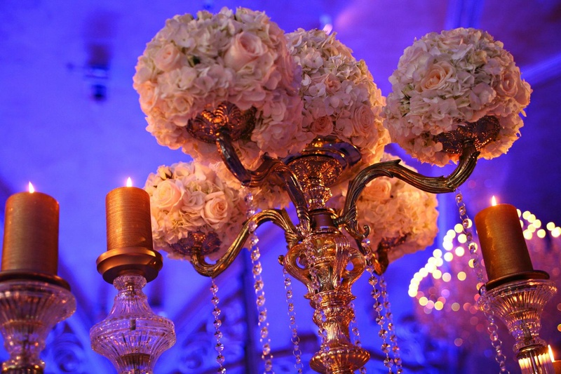 Wedding reception centerpiece of golden candelabra with light flowers surrounded by golden candles