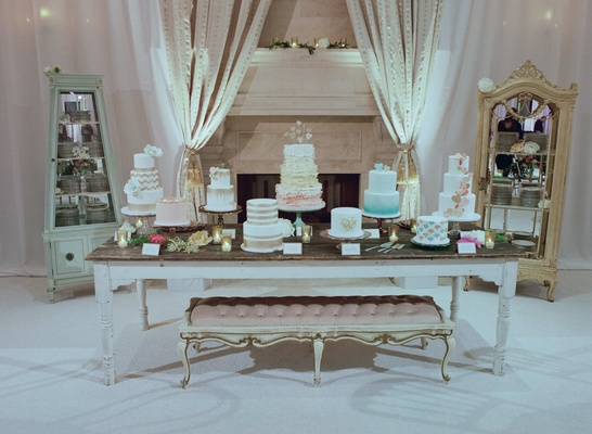 Nine wedding cakes on table in front of fireplace