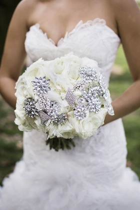 Bride in a strapless Mark Zunino dress holds a bouquet of white flowers with rhinestone brooches
