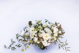 loosely structured bouquet with white roses, peonies, greenery, magnolia leaves
