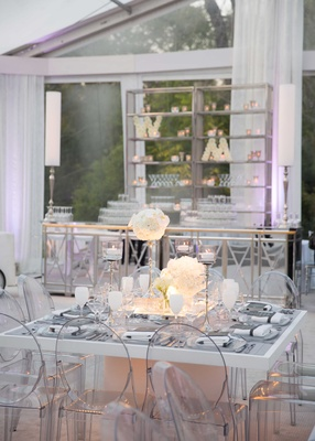 white square table with grey decor, Ghost chairs, and white goblets with ivory centerpiece flowers