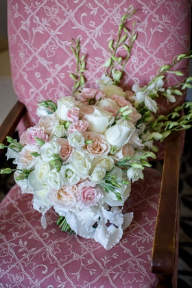 Wedding bouquet white and pink roses and tall flower accents on pink upholstered chair