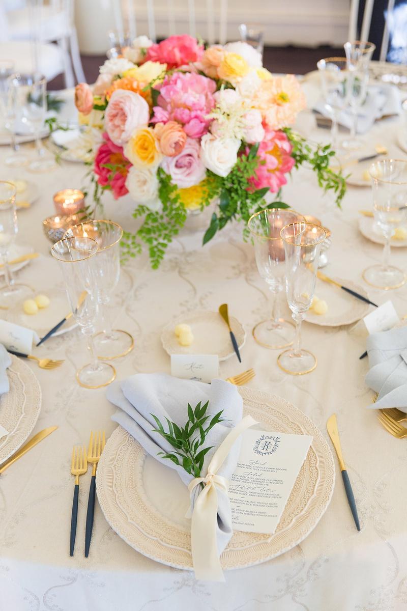 wedding reception table beige linen blue napkin flatware pink yellow orange flower centerpiece
