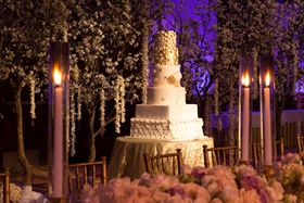 White wedding cake with two golden layers, fondant petals, surrounded by cherry blossom trees
