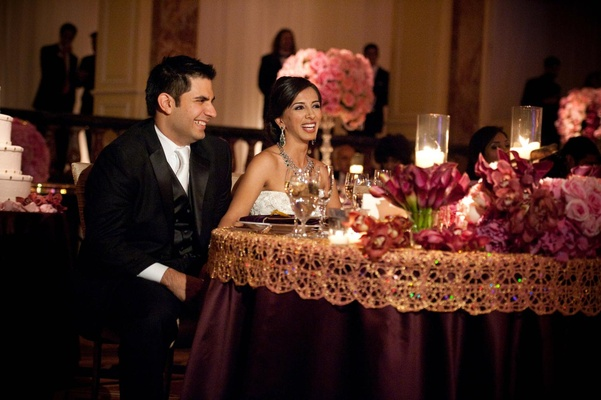 Newlyweds sitting at plum and gold table