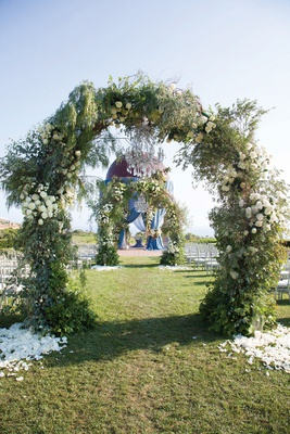 ceremony at resort at pelican hill with arches of greenery over aisle leading to rotunda