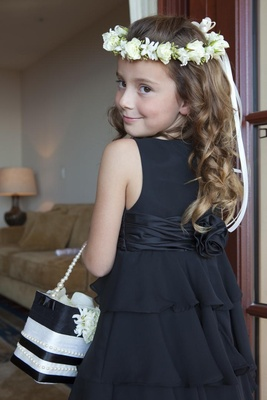 Flower girl in a black sleeveless dress with a tiered skirt and white floral halo