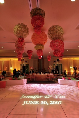 Wedding reception with green, pink, and orange flowers over the dance floor