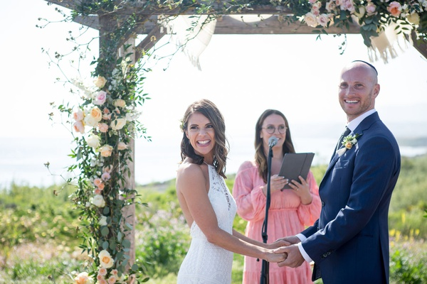 bride and groom under wood chuppah flowers greenery sister in law officiant pink dress lace halter